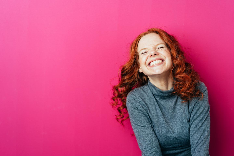 Junge Frau mit roten Haaren strahlt vor pinkfarbenem Hintergrund.