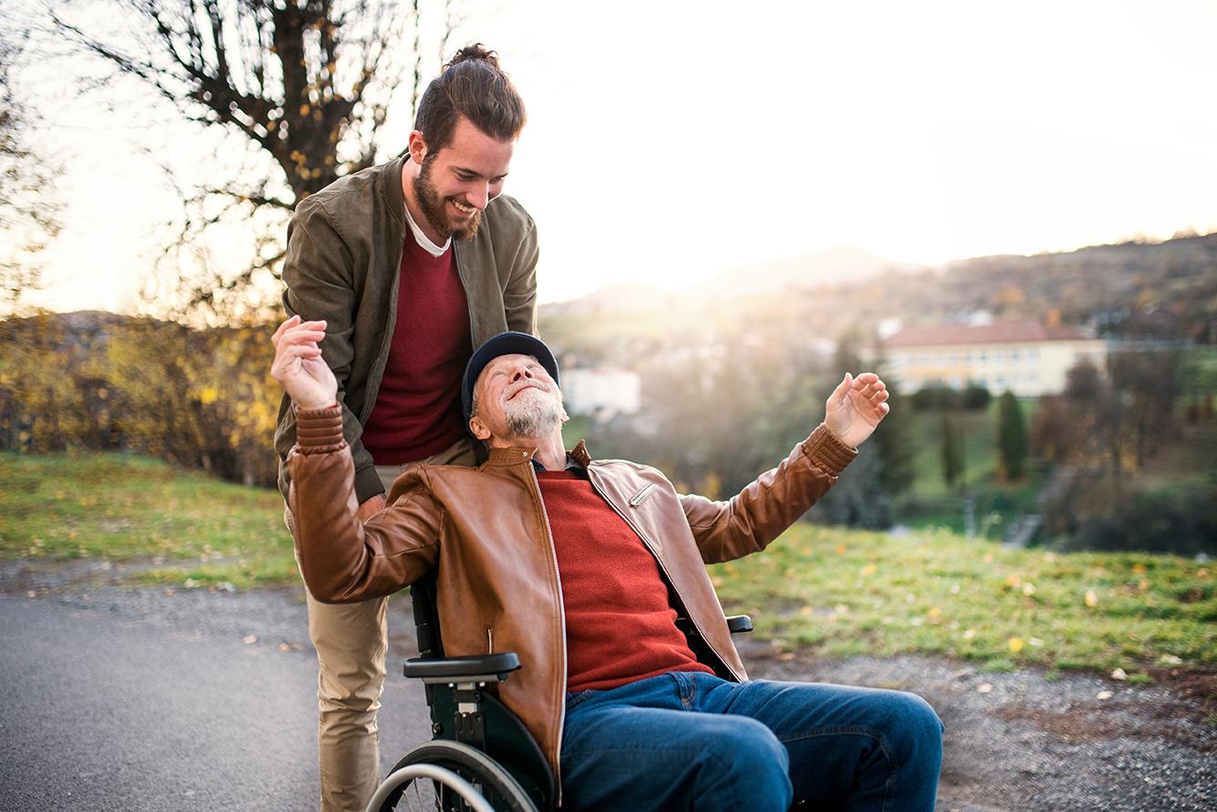 Ein junger, hilfsbereiter Mann geht mit einem Mann im Rollstuhl spazieren.