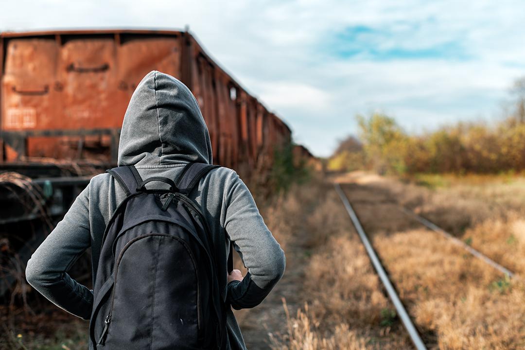 Eine junge Frau in Kapuzenpullover läuft vor der Kamera weg auf verlassenen Zugschienen neben alten Wagons.