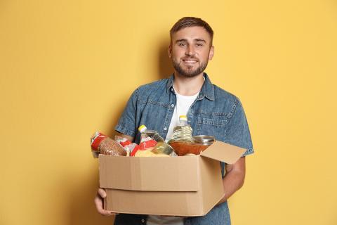 Ein junger Mann hält einen Karton voller Nahrungsmittel.