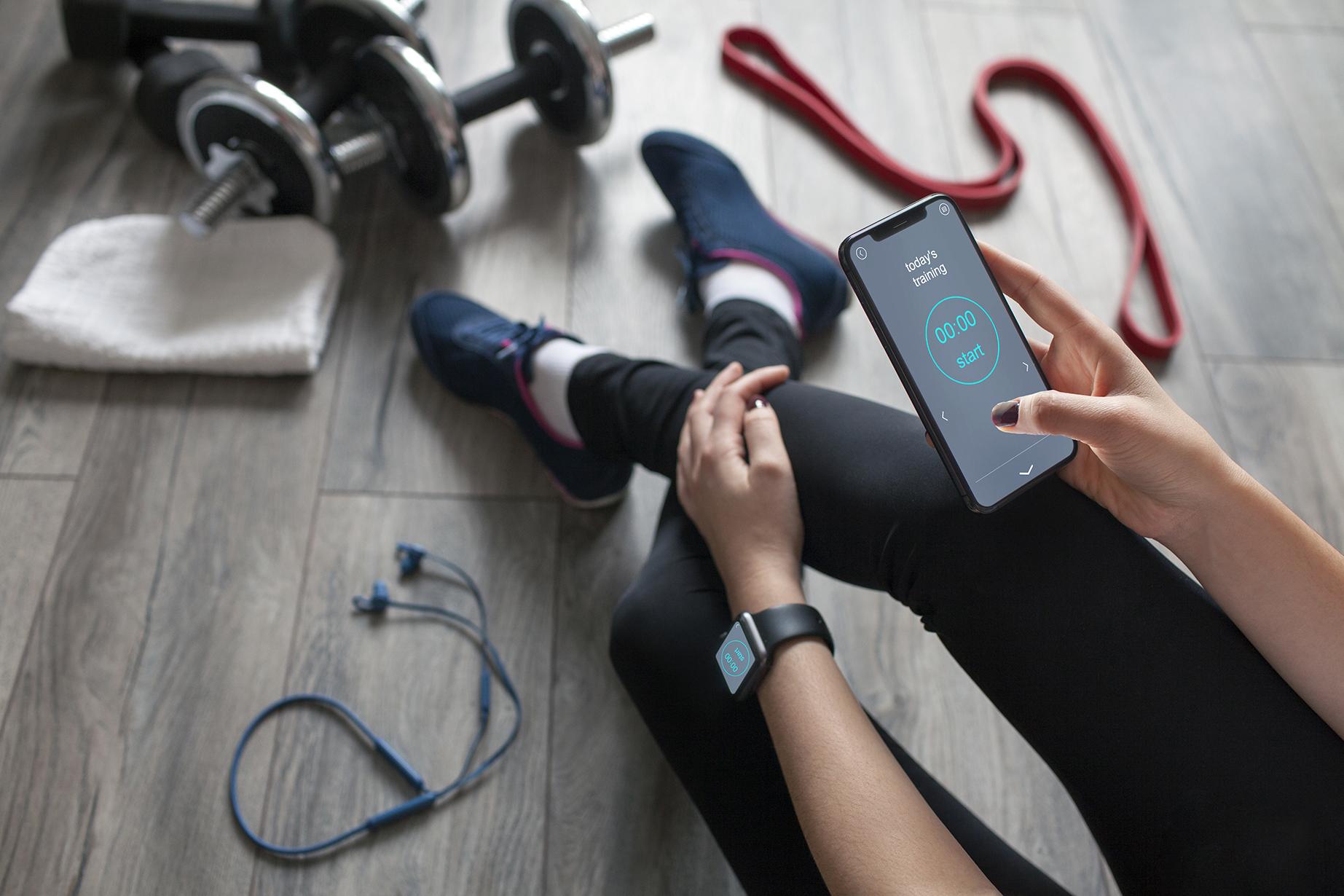 Eine Frau in Sportbekleidung hält ein Smartphone mit geöffneter Trainings-App