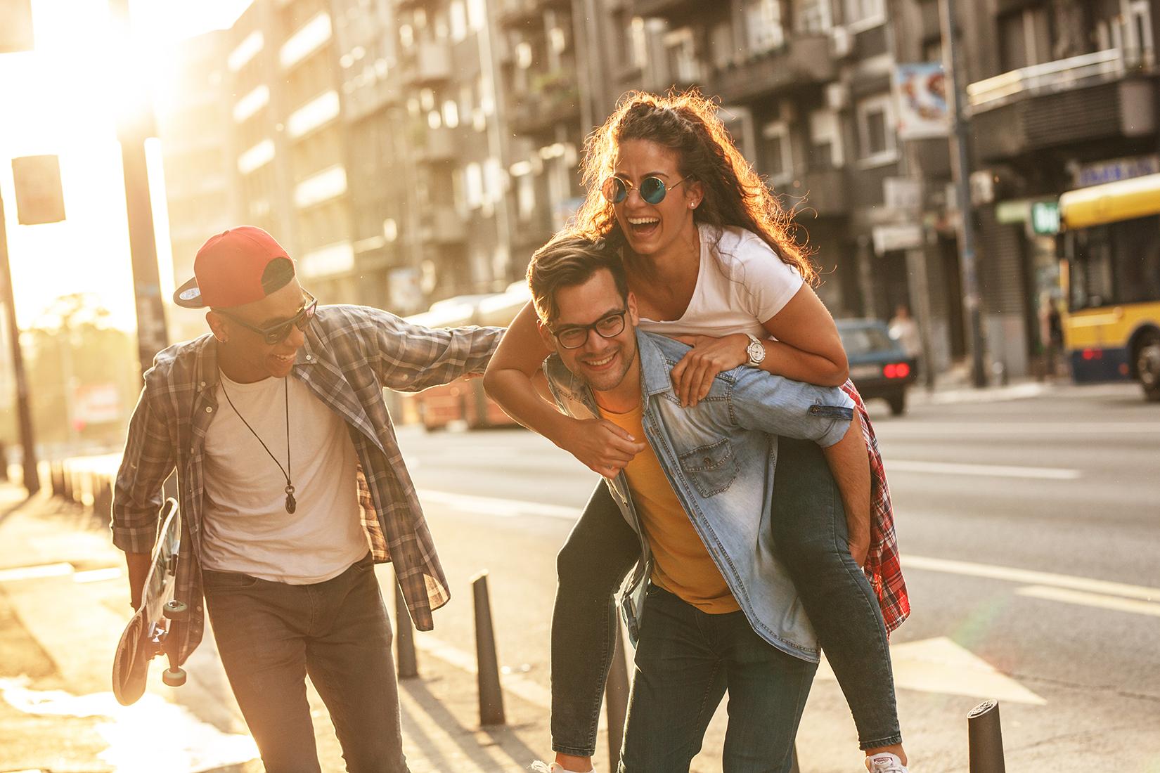 Drei Freunde albern in einer Großstadt-Szenerie. Die junge Frau sitzt auf den Schultern eines Freundes.