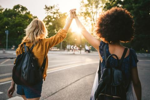 Zwei Freundinnen laufen Richtung Sonnenuntergang. Sie heben die Arme und halten sich dabei an der Hand.