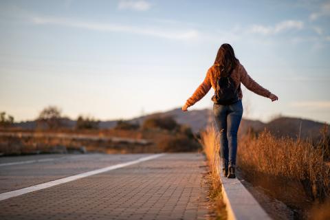 Eine junge Frau läuft auf einem Bordstein.