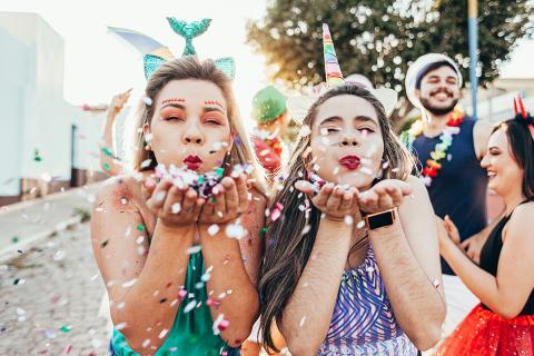 Zwei junge Frauen feiern, verkleidet als Meerjungfrau und Einhorn, Karneval.