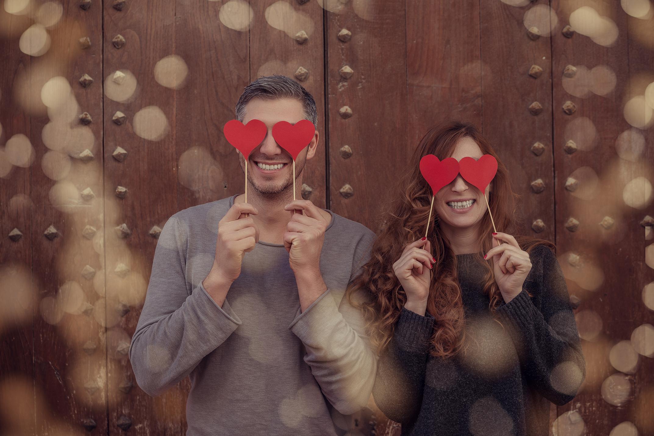 Ein Paar steht nebeneinander vor einem hölzernen Tor. Beide halten Herzen aus Pappe vor ihre Augen, angelehnt an den Emoji mit Herzaugen.