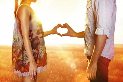 Silhouette von zwei Händen eines Liebespaares, die ein Herz formen.