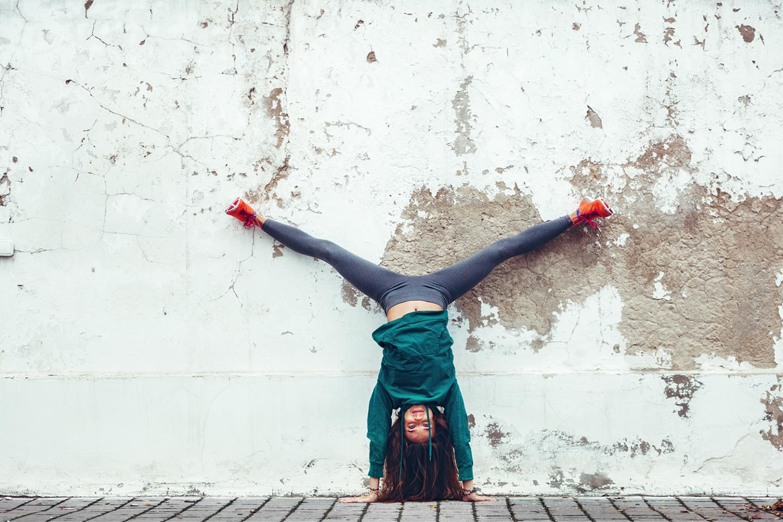 Eine junge Frau macht vor einer Wand einen Handstand.