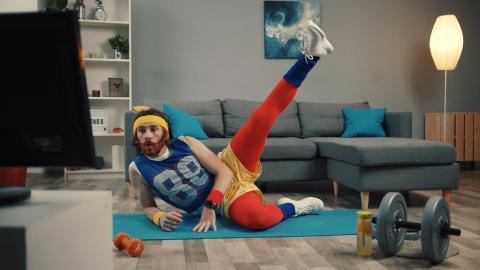 Ein in lustiger Sportkleidung gekleideter Mann macht Gymnastik vor dem Fernseher.