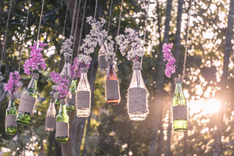 Selbstgemachte Dekoration. Flaschen mit Blumen mit Kordeln an Bäumen befestigt.