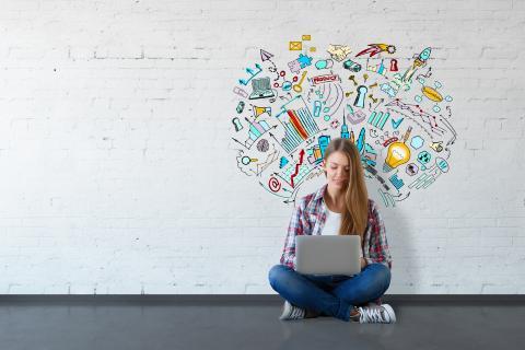 Eine junge Frau sitzt mit einem Laptop auf dem Boden. Auf der Wand hinter ihr illustrierte Symbole für Digitales.