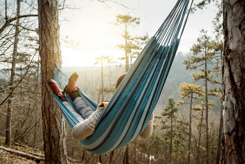 Ein junger Mann entspannt im Wald auf der Spitze eines Berges auf einer Hängematte.