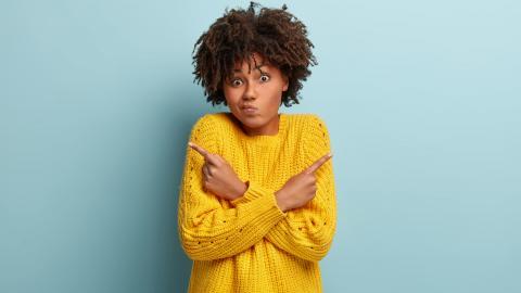 Eine junge verunsicherte Frau mit lockigem Haar kreuzt ihre Unterarme vor sich. Ein Zeigefinger zeigt nach oben Links, der andere nach oben Rechts. Sie kann sich nicht entscheiden.