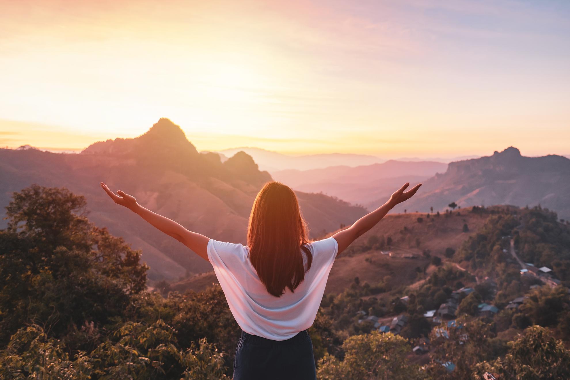 Eine junge Frau in Sommerkleidung erhebt grüßend ihre Hände vor dem Sonnenaufgang an einer beeindruckenden, weiten Berglandschaft.