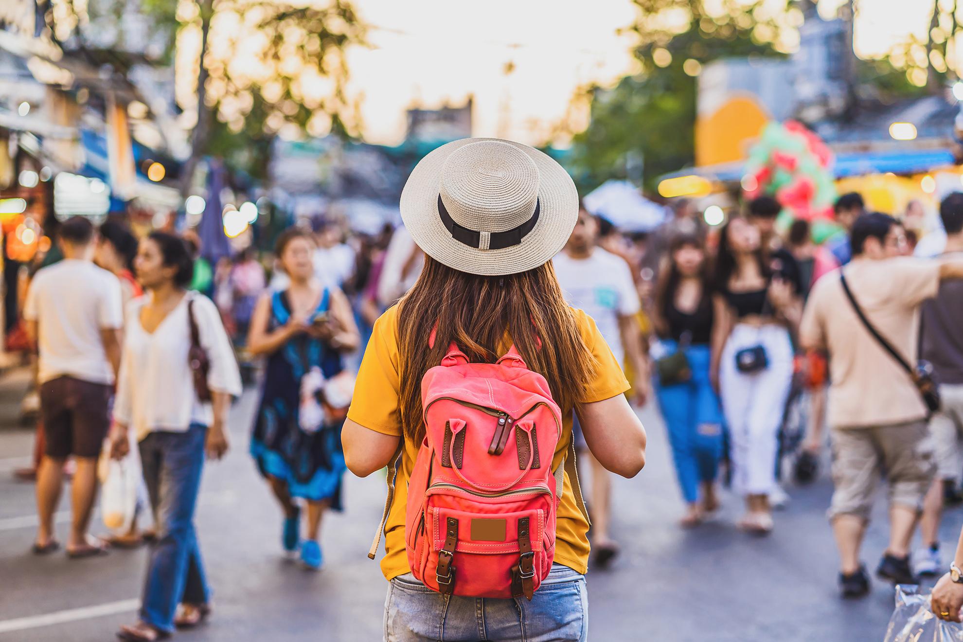 Eine junge Backpackerin erkundet die Straßen von Bangkok.