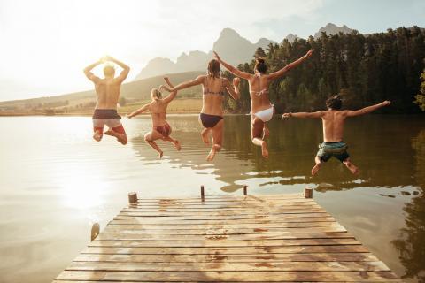 Fünf junge Freude springen von einem Steg in den See. Es ist ein schöner, sonniger Tag.