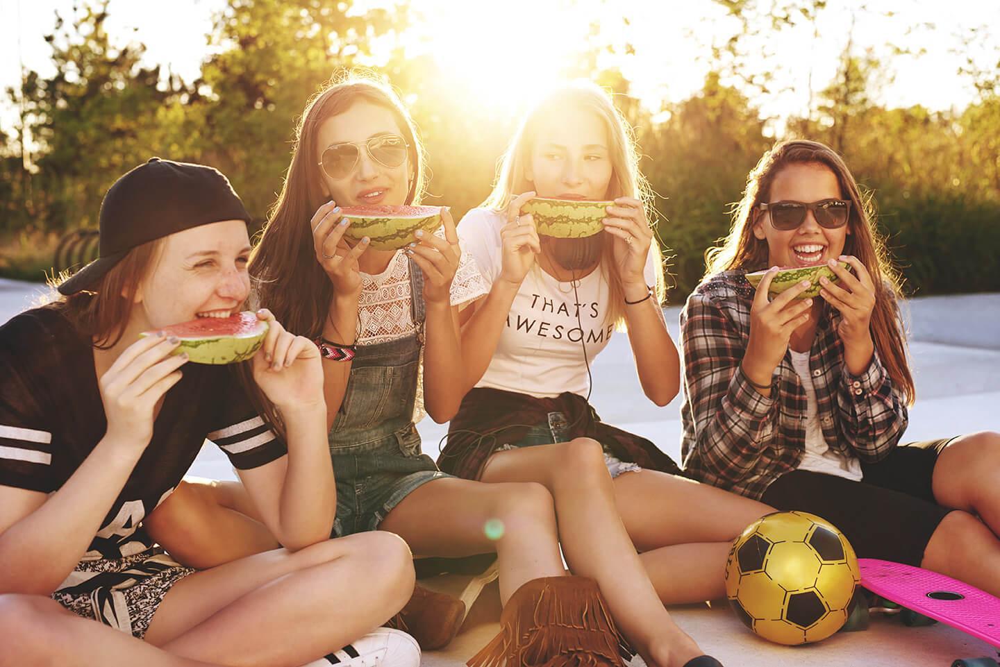 Vier Teenager-Mädchen teilen sich an einem sonnigen Sommerabend Wassermelone.