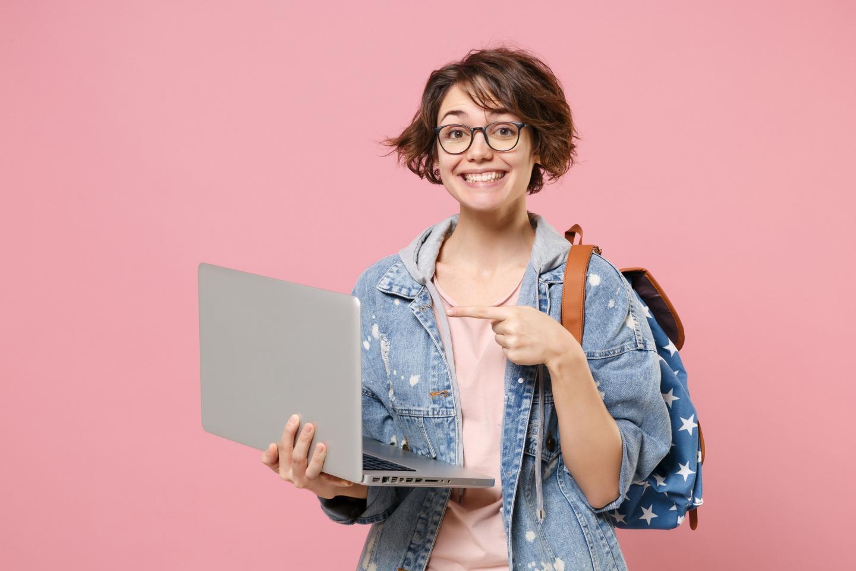 Ein Mädchen zeigt überzeugt und zufrieden auf ihren Laptop.