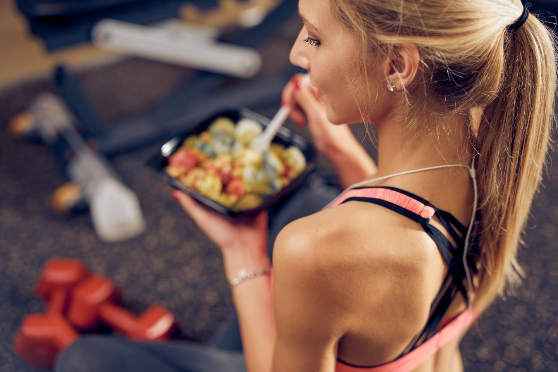 Junge Frau mit gesundem Snack im Fitnessstudio