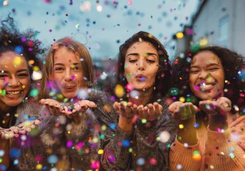 Mädchen feiern und pusten Konfetti