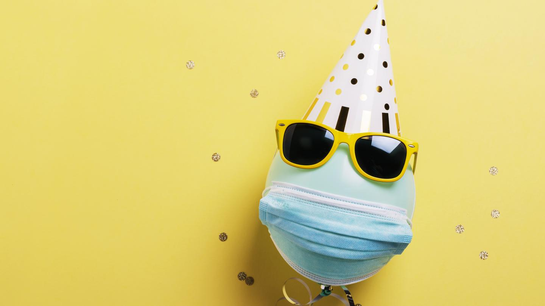 Luftballon mit Sonnenbrille, Partyhut und Mund-Nasen-Schutz