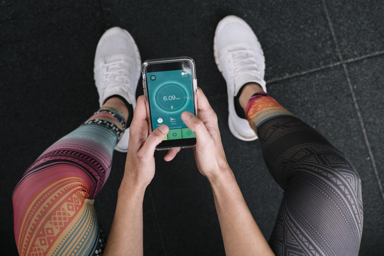 Frau in Sportkleidung benutzt Fitness-App