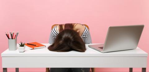Junge Frau sitzt gestresst an Schreibtisch und hat Kopf auf Tischplatte gelegt